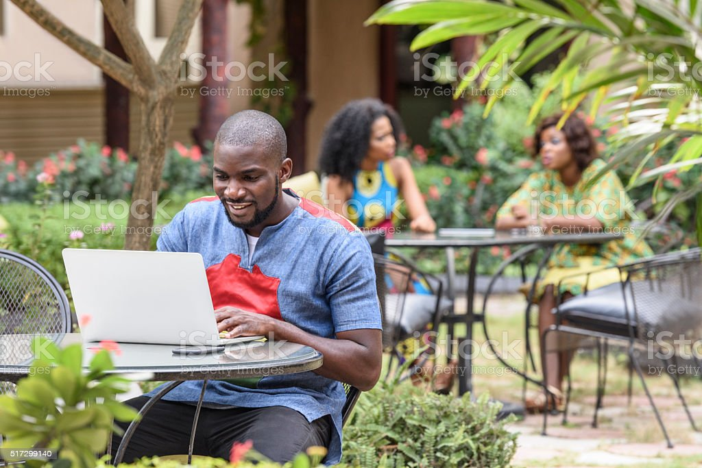Young African man using laptop in cafe garden using stock photo