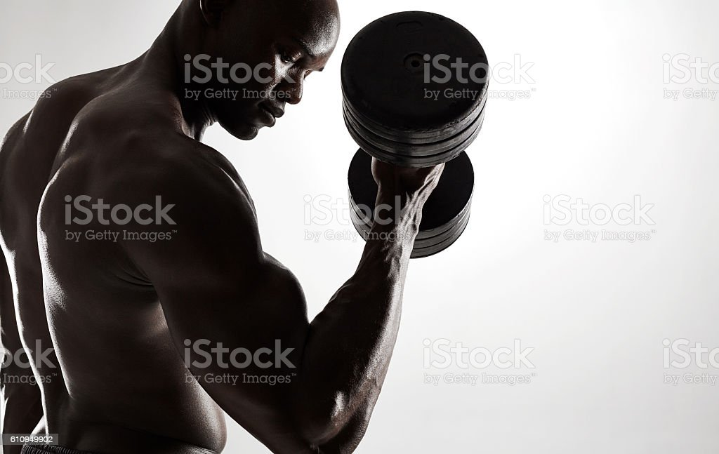 Young african man working out with dumbbells stock photo
