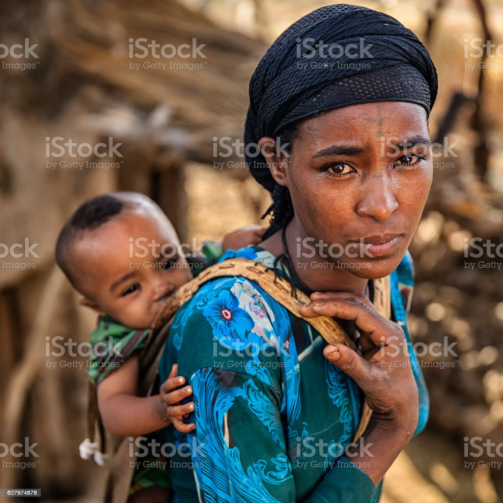 Young African mother carrying her baby on back, East Africa stock photo