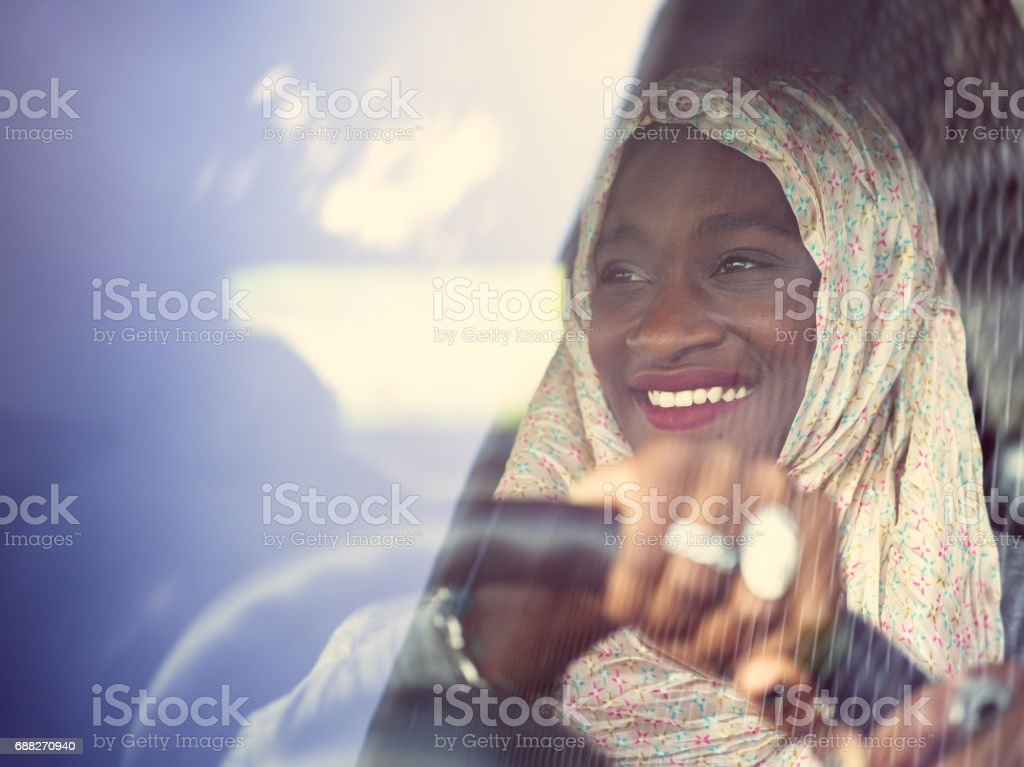 Young African Muslim woman driving a car stock photo