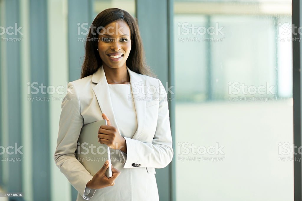 young african office worker holding laptop stock photo