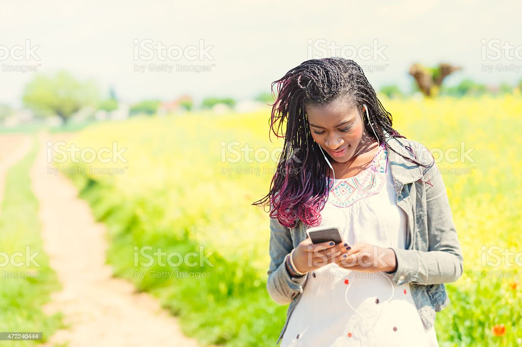 Young African woman checking for messages stock photo