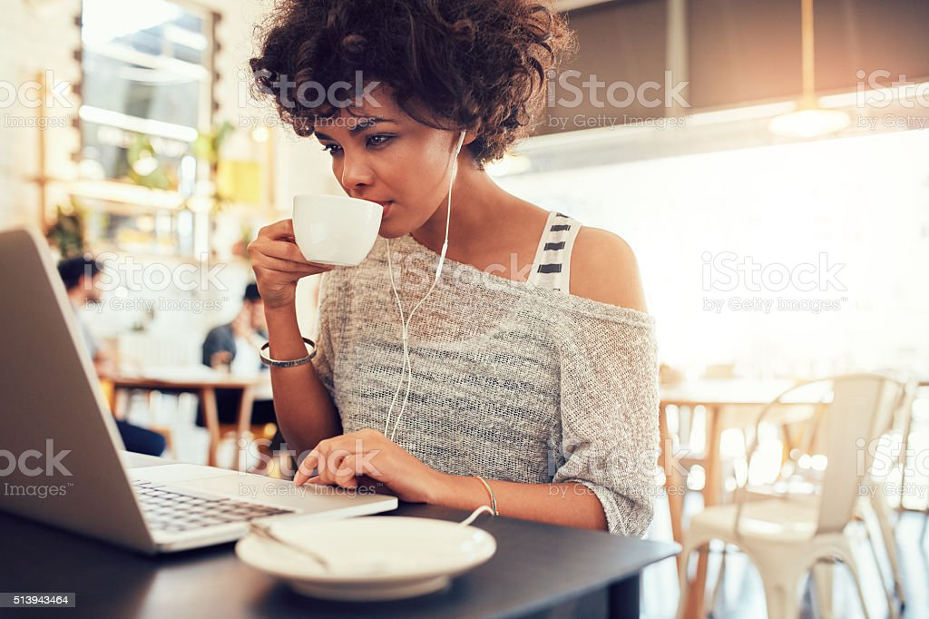 Young african woman drinking coffee and using laptop at cafe stock photo