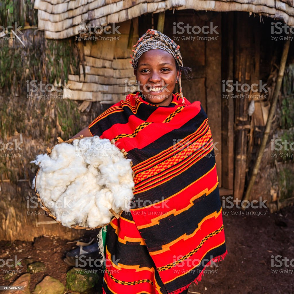 Young African woman holding basket of wool, East Africa stock photo