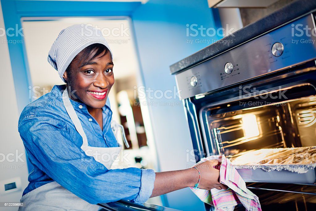 Young African woman in kitchen stock photo
