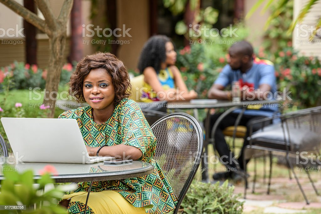 Young African woman looking to camera using laptop stock photo