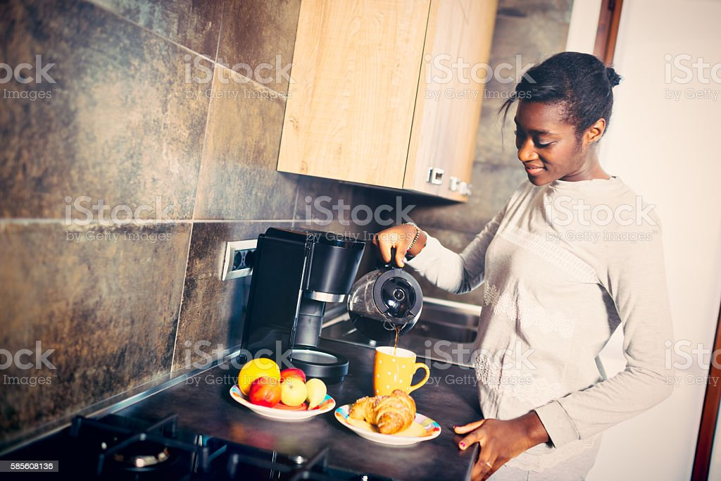 Young African Woman making coffee for breakfast stock photo