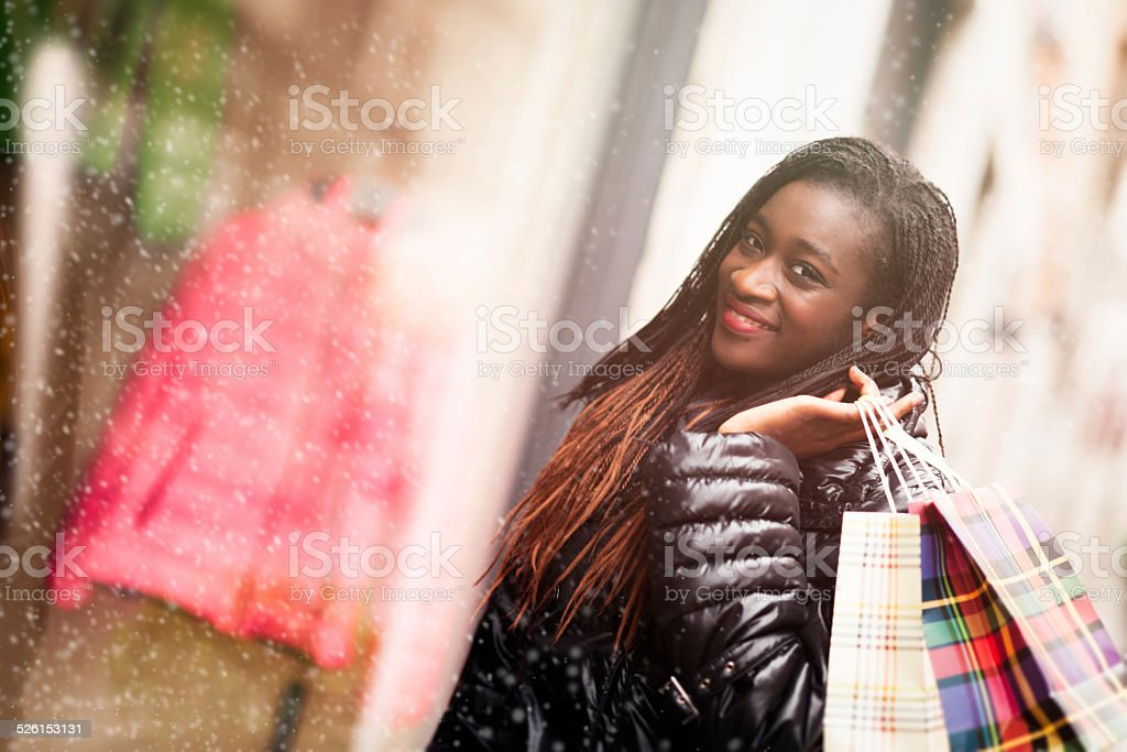 Young African woman on the street with shopping bags stock photo