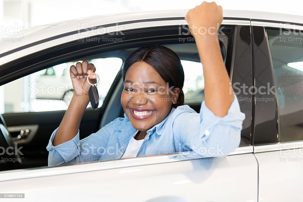 young african woman showing her new car key stock photo