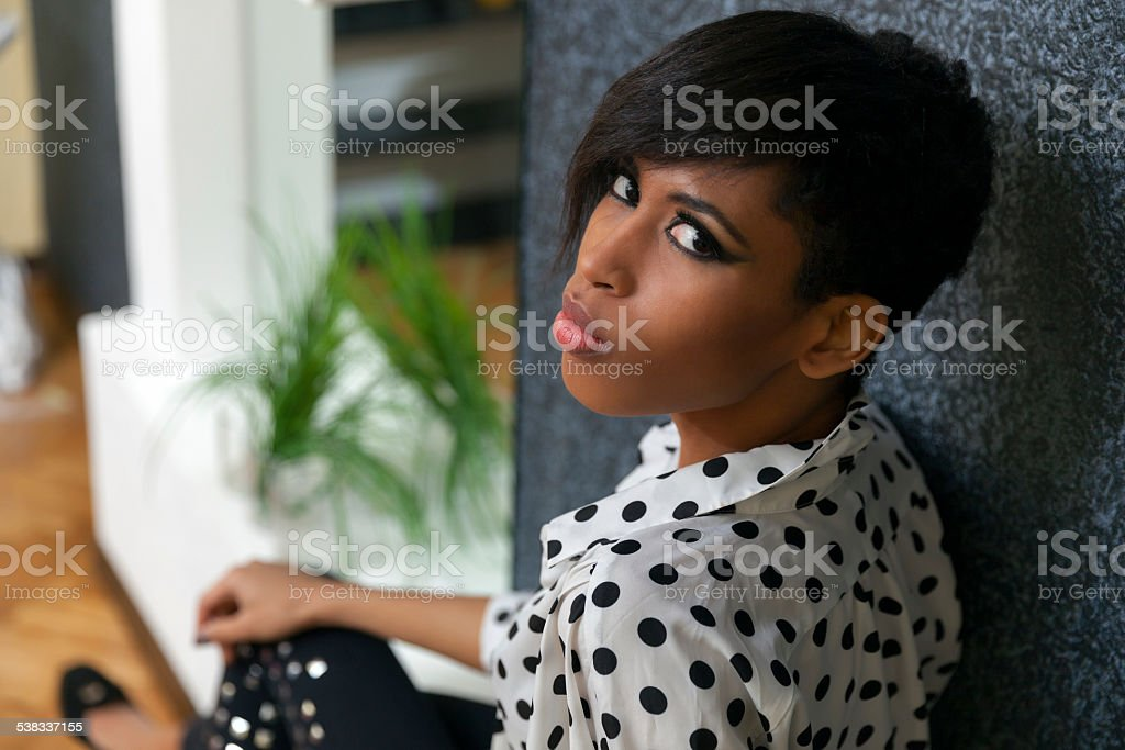 Young African woman sit sideways looking up at camera stock photo