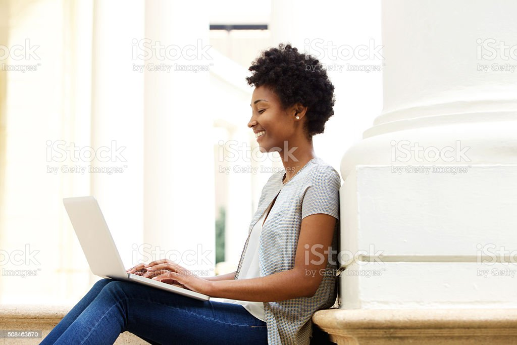Young african woman sitting outside using laptop stock photo