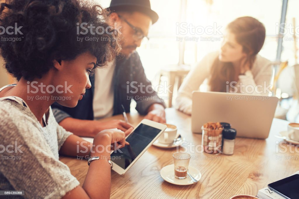 Young african woman using digital tablet with friends at cafe stock photo