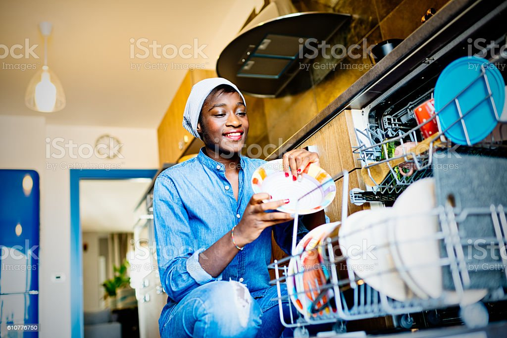 Young African woman using dishwasher in domestic kitchen stock photo