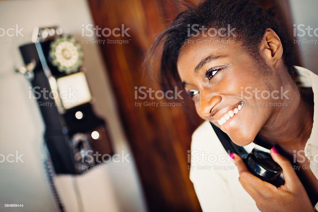 Young African Woman using retro revival phone stock photo