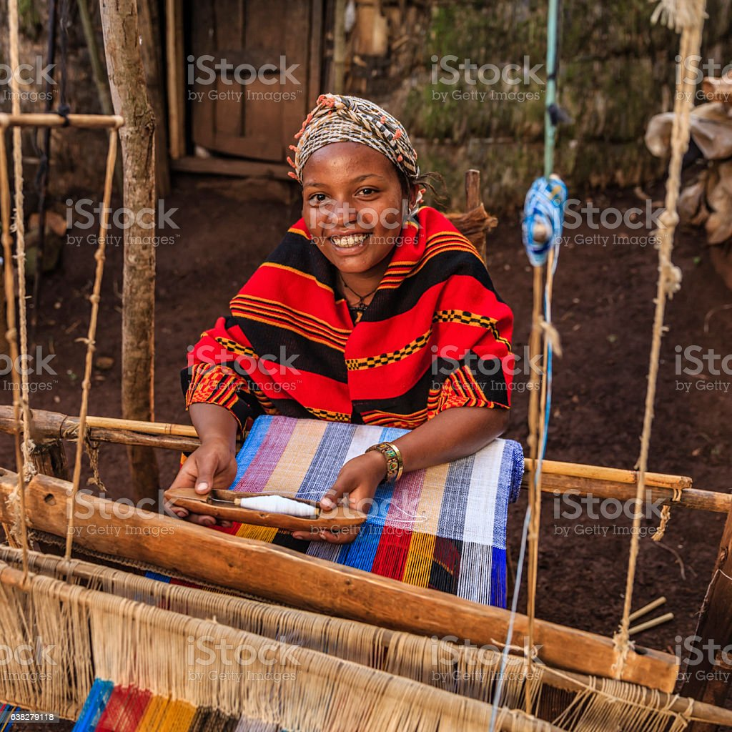 Young African woman weaving a colorful scarf, Ethiopia, East Africa stock photo