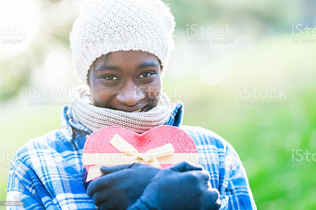 Young African woman with gift box stock photo