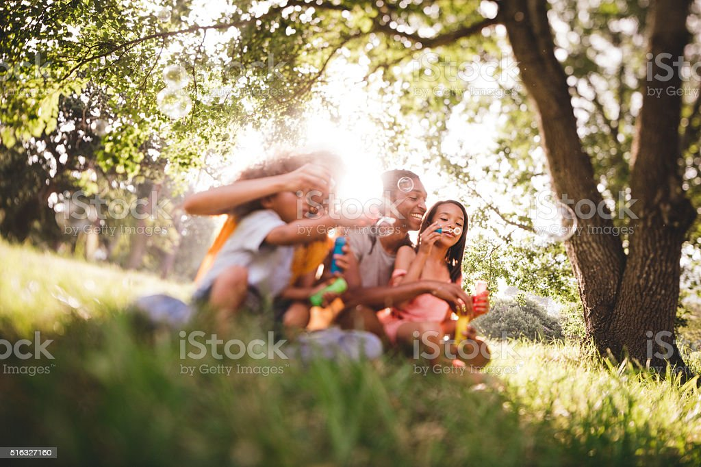 Young african-american family blowing bubbles and laughing toget stock photo