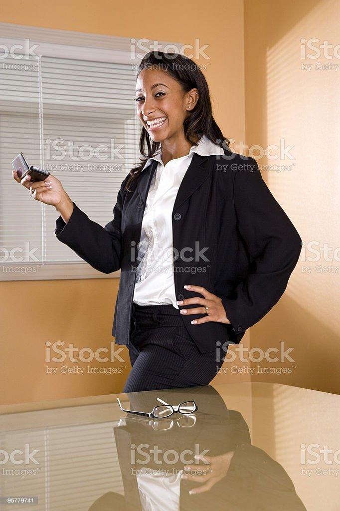 Young African-American mujer en la oficina, sala de juntas SMS a un teléfono móvil foto de stock libre de derechos
