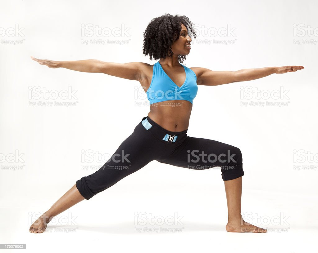 young African-American woman standing in yoga warrior pose royalty-free stock photo