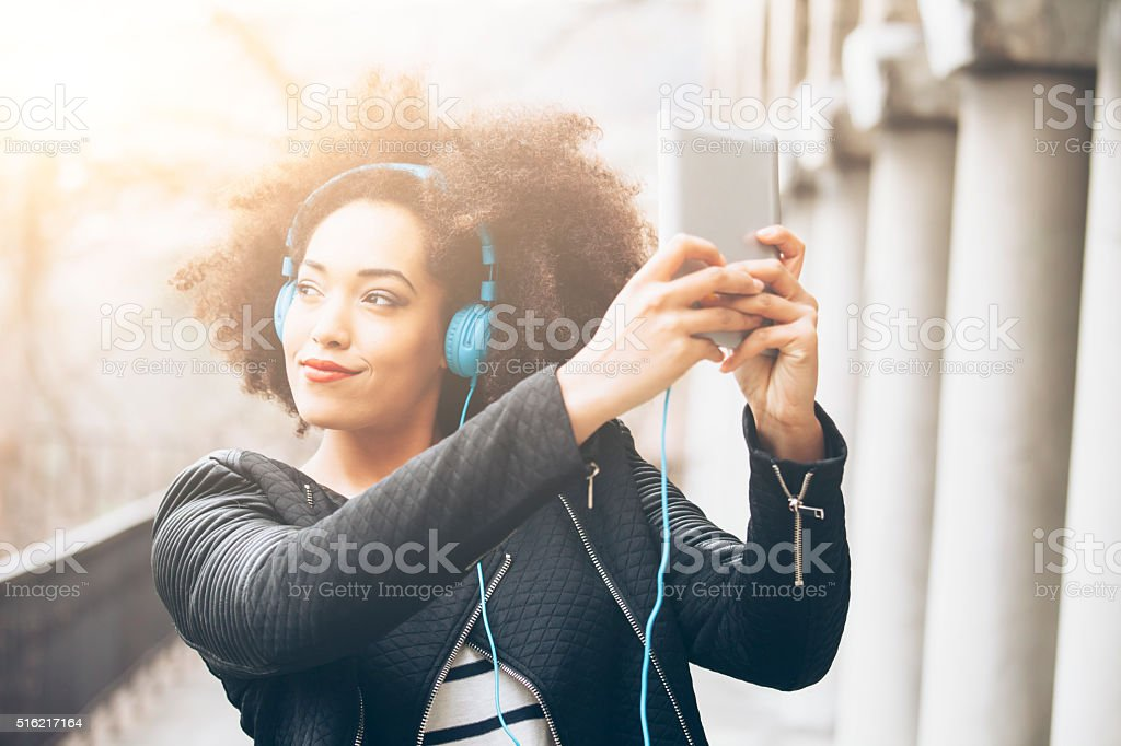 Young afro woman listening music stock photo