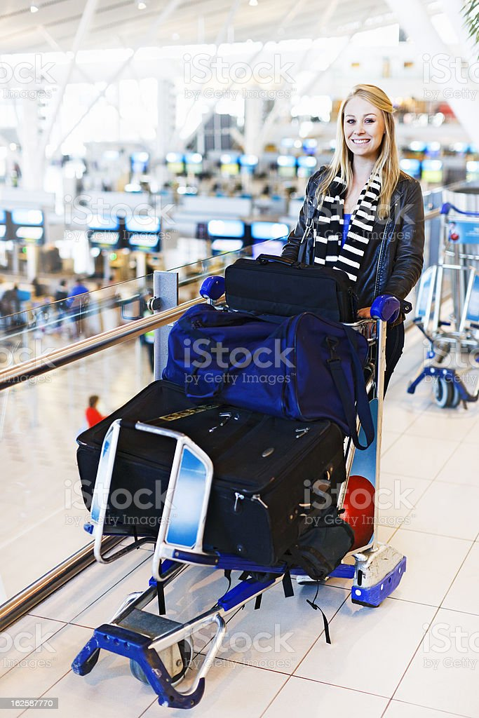 Young air traveler with baggage stands above check-in counters stock photo