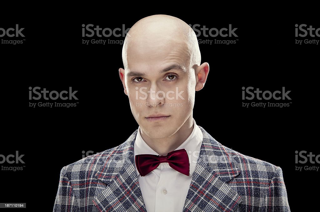 Young alluring bald professor with red bow tie black isolated royalty-free stock photo