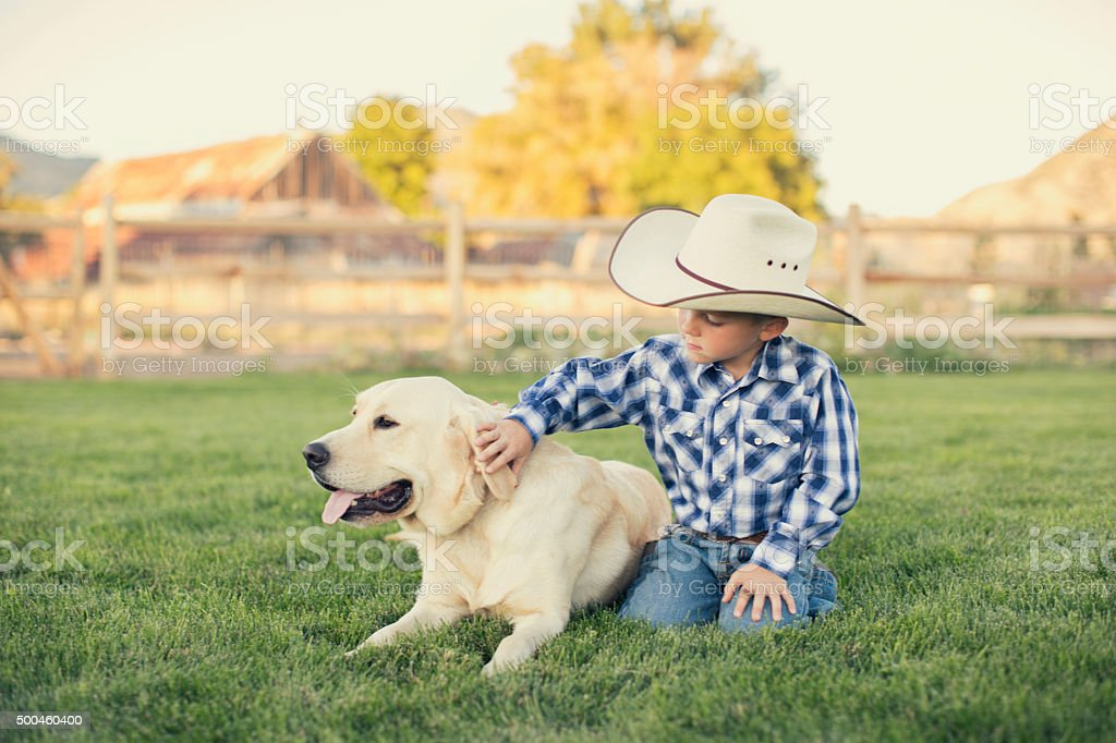 Young American Cowboy Petting His Dog stock photo