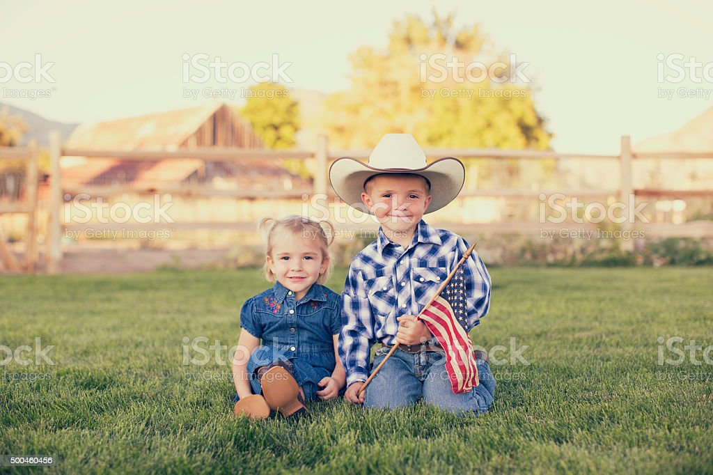 Young American Cowgirl and Cowboy with US Flag stock photo