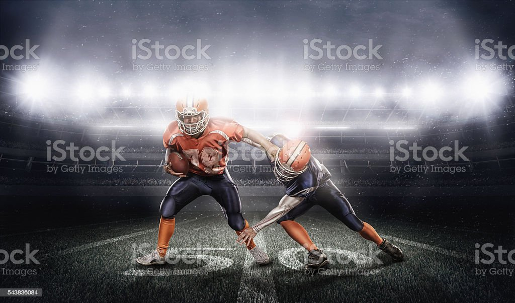 Young american football players in action on stadium with ball stock photo