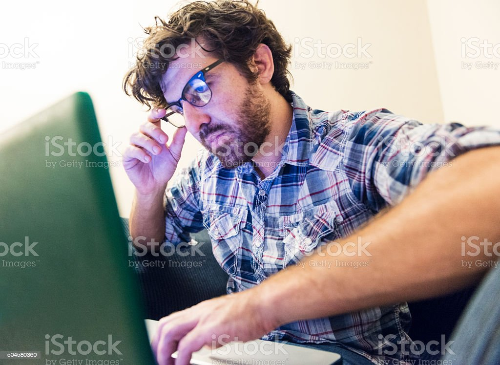 Young American with Beard Looks Serious Reading on Laptop Computer stock photo