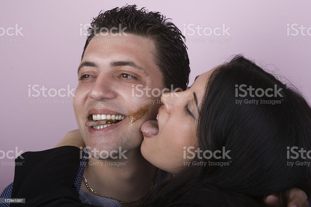 Young amorous couple playfully eating chocolate royalty-free stock photo
