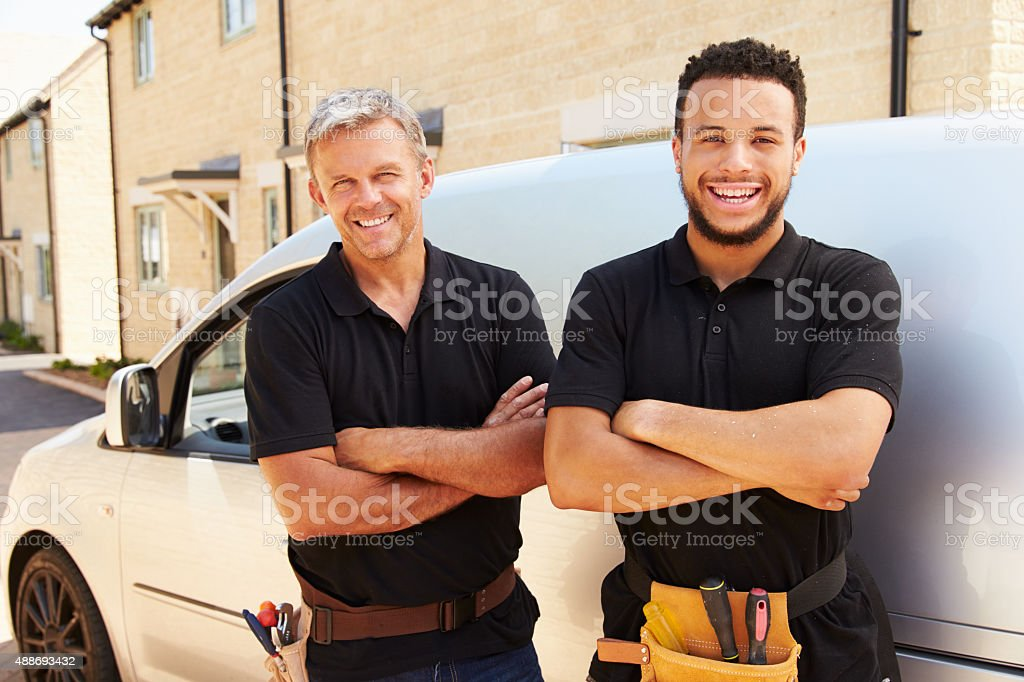 Young and a middle aged tradesman by their van stock photo