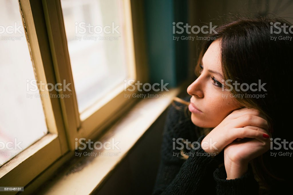 Young and attractive female looking through window stock photo