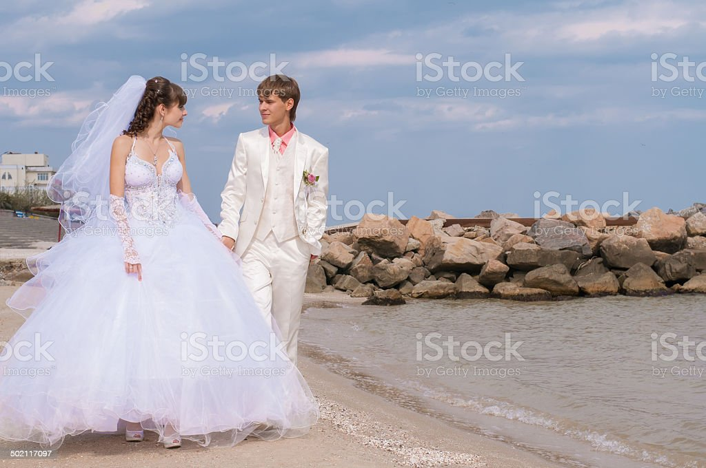 Young and beautiful bride and groom on the beach stock photo