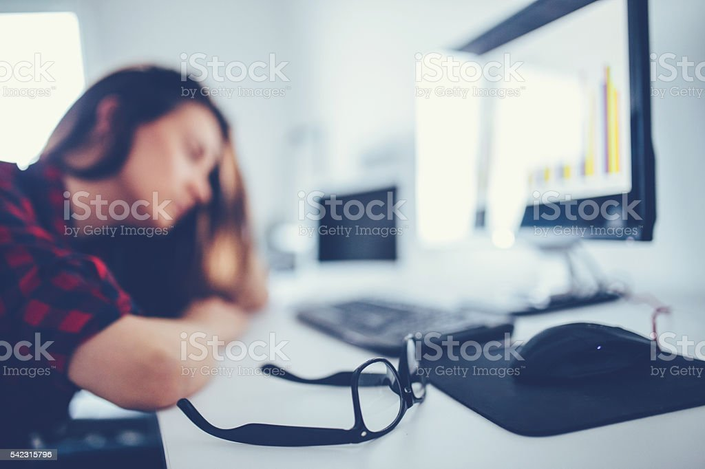 Young and beautiful businesswoman tired from work in the office. stock photo
