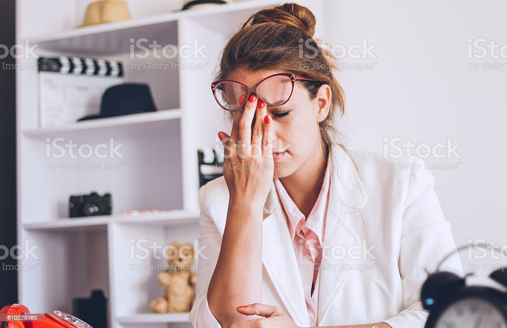 Young and beautiful businesswoman tired from work in the office stock photo