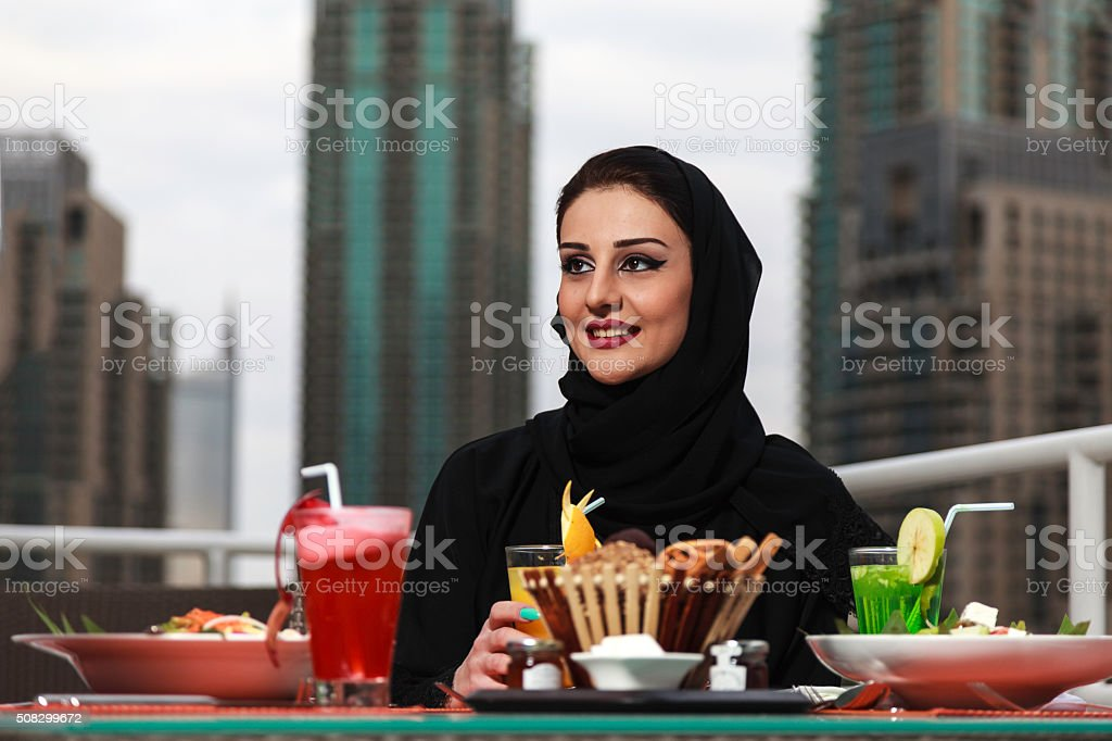 Young and beautiful Emirati woman sitting by the canal stock photo