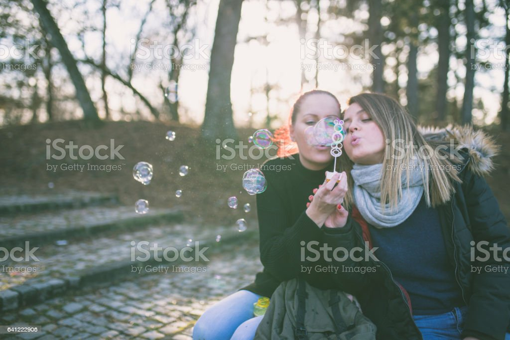 Young and beautiful girls blowing bubbles stock photo