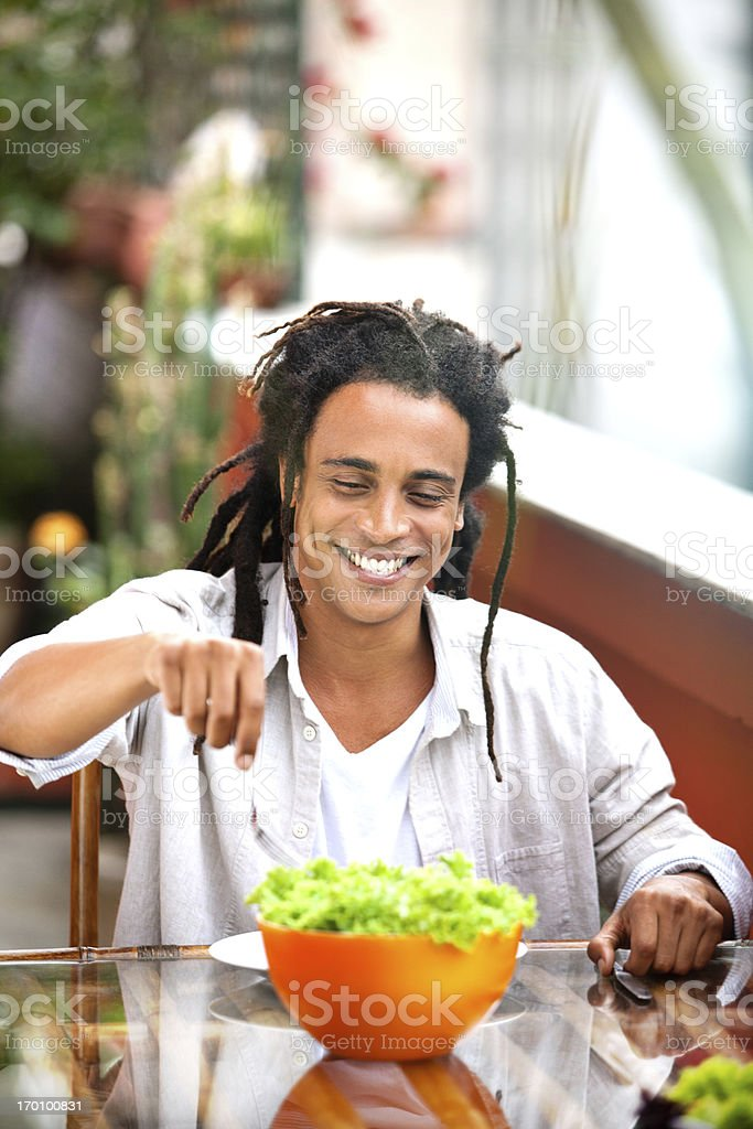 Young and beautiful smiling man eating salad on the table. royalty-free stock photo