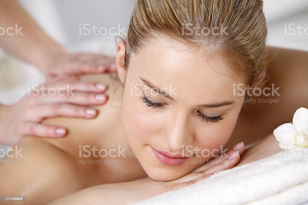 Young and beautiful woman enjoying having back massage royalty-free stock photo