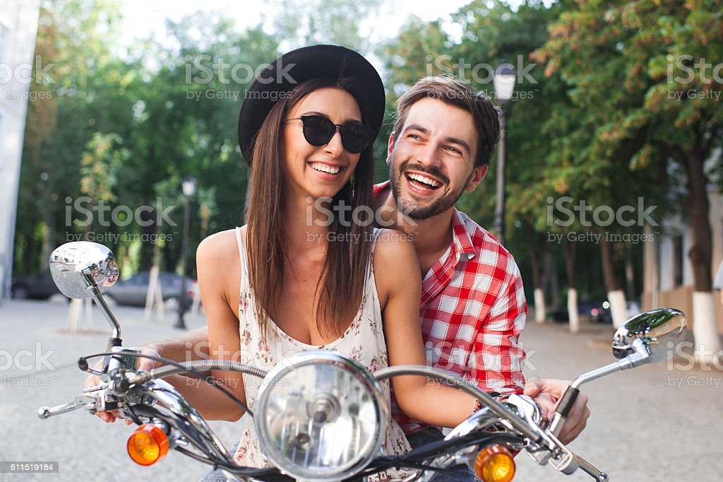 Young and carefree couple learning to drive a scooter stock photo