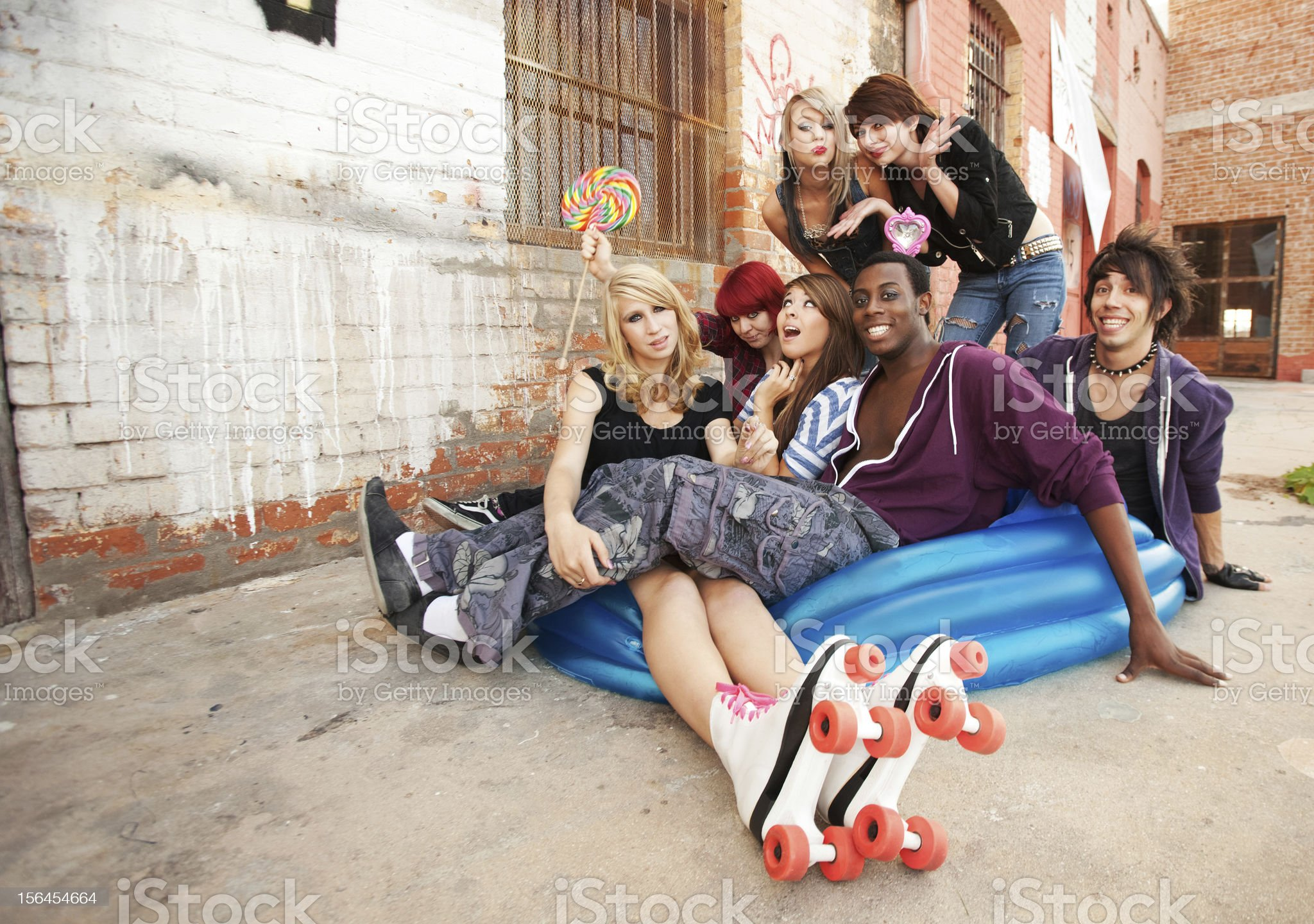 Young and crazy teens playing in a blue inflatable pool royalty-free stock photo