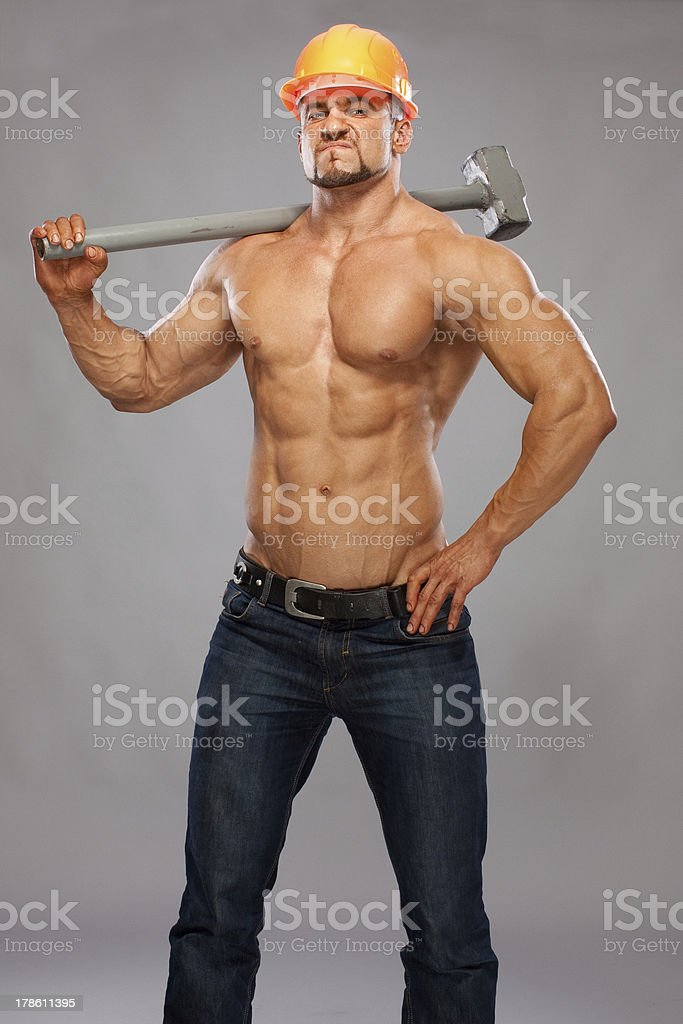 Young and handsome builder with a sledgehammer royalty-free stock photo