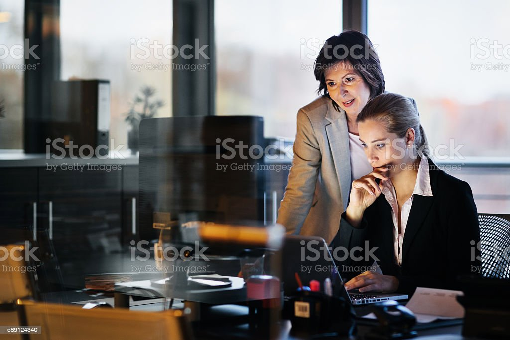 Young and Mature Business Woman Working Late stock photo