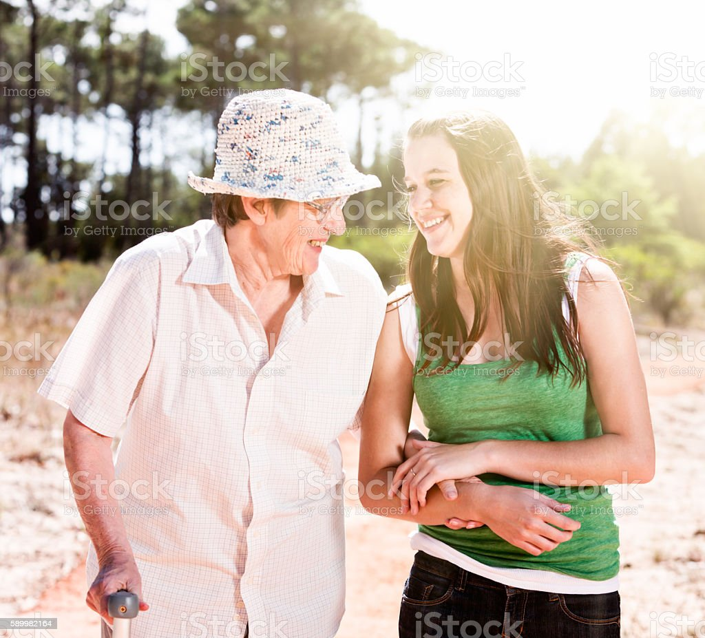 Young and old woman, arm-in-arm, walk, smiling at each other stock photo