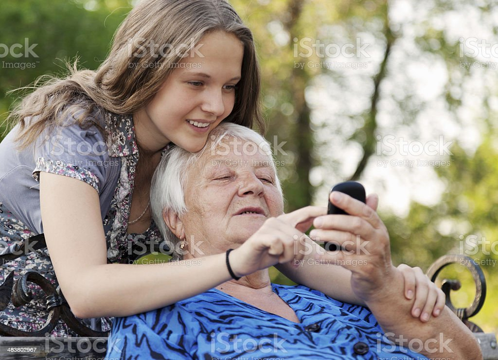 Young and old woman examine image in phone royalty-free stock photo