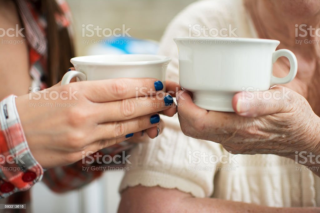 Young and old women holding cups. stock photo