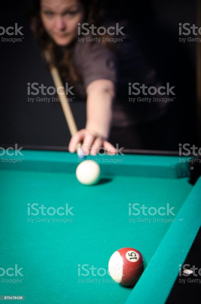 Young and pretty woman using cue stick to hit cue ball during pool...