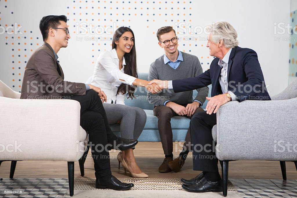 Young and Senior Business People Shaking Hands stock photo