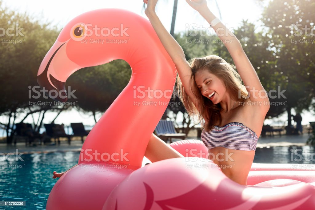 Young and sexy girl having fun and laughing on an inflatable giant pink flamingo pool float mattress in a bikini. Attractive tanned woman lies in the sun on vacation stock photo